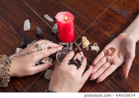 A Gypsy woman performs a love spell. A clairvoyant palmist reads by hand with a candle. A fortune teller predicts the fate of love with wedding rings, a magic ball, lighted candles and magic stones. 64658654