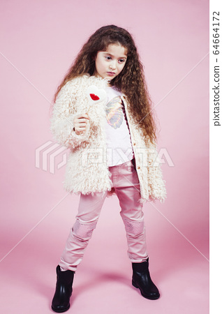little cute girl with candy on pink background posing emotional, lifestyle people concept 64664172