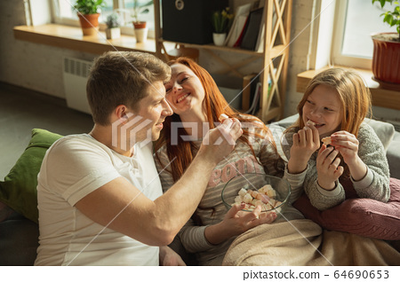 Family spending nice time together at home, looks happy and cheerful, watching TV 64690653