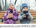 Two cute adorable siblings children sitting on wooden bench and drinking hot chocolate, tea or cocoa from paper cups during walk at city street park or backyard outdoors. Brother and sister enjoy fun 64691180
