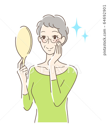 A woman looking at a hand mirror with a smile 64692901