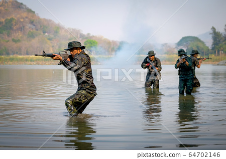 One Asian soldier man holds gun and target to the the front walk in front of his team 64702146