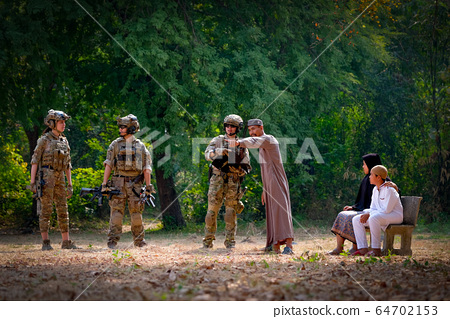 Muslim man stay with family and help by point and guide the way for soldier team 64702153