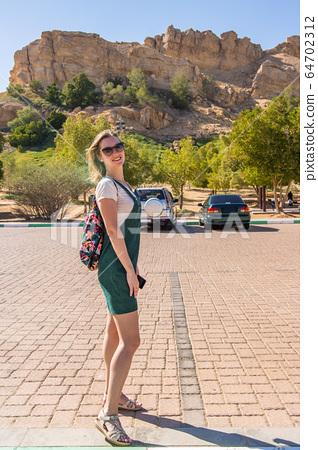 Tourist girl posing near hot thermal springs in the Arab Emirates near Ain Al. 64702312