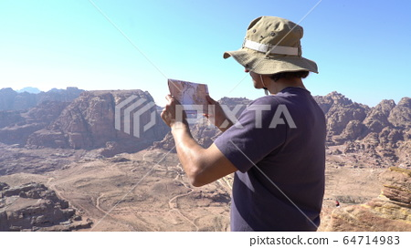Hiker looking at map from mountain top Aerial shot of hiker looking at map from mountain top. Man 64714983