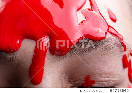 Photo of woman's forehead with draining red paint, close-up 64718640