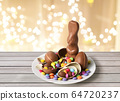 chocolate bunny, eggs and candies over lights 64720237