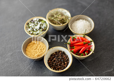 bowls with different spices on slate stone table 64720662