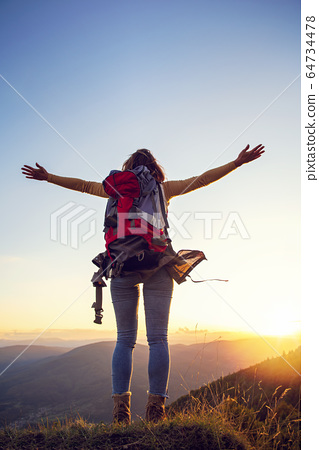cheering woman hiker open arms at mountain peak 64734478