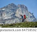 Cheerful traveler hiking in mountains. 64758592