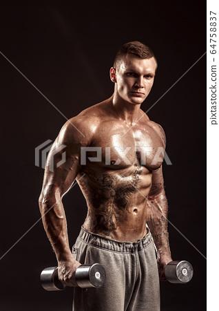 Serious tattoed shirtless athlete lifting metal dumbbells training on dark background 64758837