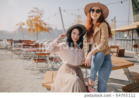 Fashionable girl in beige hat sitting on table 64765112