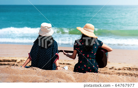 Friends spending time on the beach with a guitar 64767977