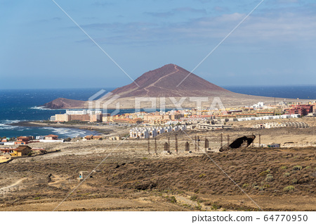 Old satellite dish antenna in dry arid land near El Medano, Tenerife, Canary Islands, Spain, telecommunication and wireless communication security concept 64770950
