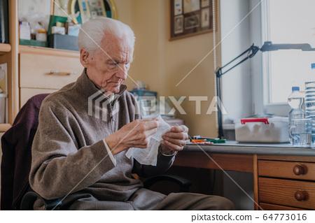 Senior preparing dressing, cuts gauze 64773016
