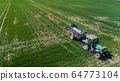 Agriculture Tractor Working in Field Spraying Herbicides 64773104