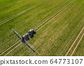 tractor spraying herbicides on field, Tractor Spraying Chemicals on Field - GMO Crops. 64773107
