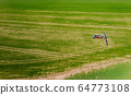 tractor spraying herbicides on field, Tractor Spraying Chemicals on Field - GMO Crops. 64773108