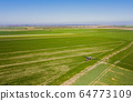 tractor spraying herbicides on field, Tractor Spraying Chemicals on Field - GMO Crops. 64773109