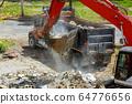 Backhoe excavator scoop loading from building in 64776656