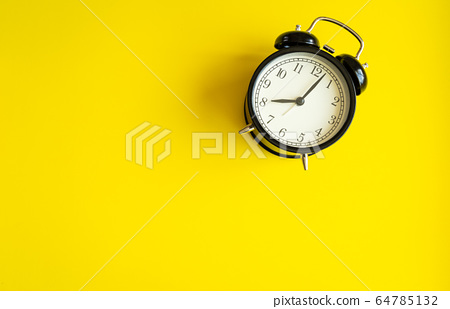black alarm clock from 7 a.m. to 8 a.m. with bright yellow  background and shadows from the changing light of the sun's movements in morning and working hours concept front shot 64785132