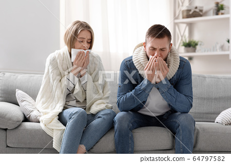 Sick man and woman coughing at home interior 64797582