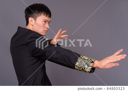 Studio shot of young Chinese man against gray background 64803323