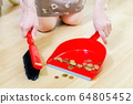 Woman sweeping coins on floor 64805452