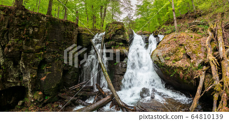 huge waterfall in the forest. multiple cascade of 64810139