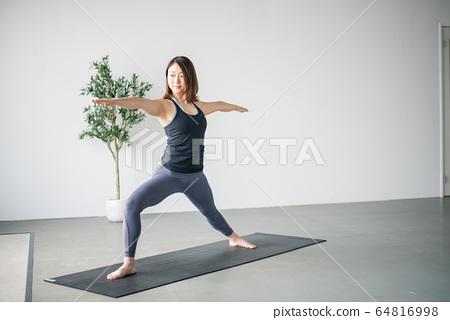 Woman practicing yoga in studio. 64816998