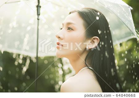 漂亮的女人雨傘弄濕的人素材 64840668
