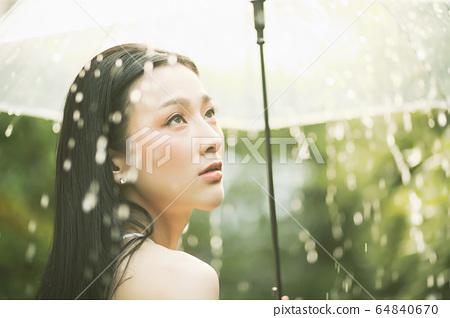 漂亮的女人雨傘弄濕的人素材 64840670