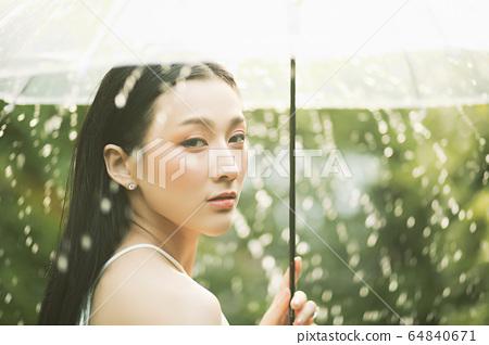 漂亮的女人雨傘弄濕的人素材 64840671