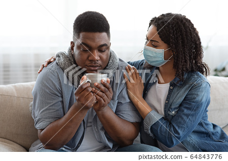 Caring Black Wife Looking After Her Ill Husband With Coronavirus At Home 64843776