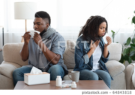 Family Suffering From Coronavirus At Home. Sick Black Couple Coughing On Couch 64843818