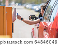 man pays by credit card parking in the parking meter 64846049
