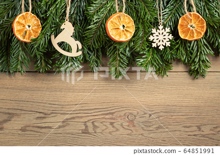 Zero waste and eco friendly christmas concept. Christmas tree branches with natural decorations on a wooden wall. Horizontal banner with copy space 64851991
