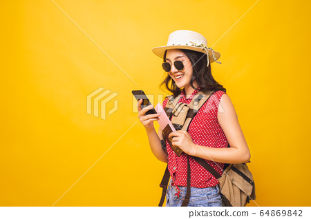 Woman cheerful enjoying shopping online by smartphone and credit card in studio yellow background. 64869842