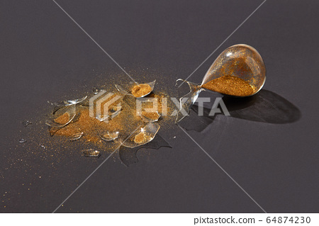 Broken antique hourglass with golden sand on a black background. 64874230