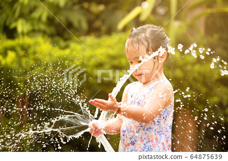 Cute little girl playing a rubber hose spraying 64875639