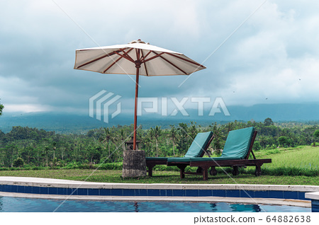 basein with sunbeds and an umbrella from the sun 64882638