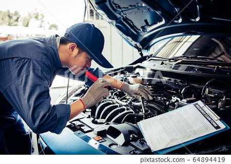 Car mechanic technician holding flashlight 64894419