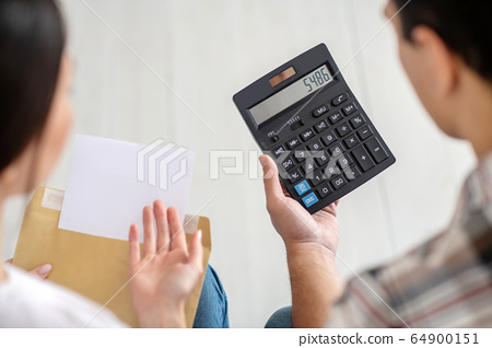 Close-up of male and female hands holding calculator and envelope 64900151
