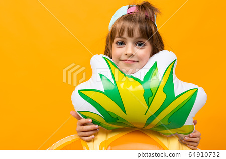 happy child with a baseball cap in a swimsuit with a pineapple rubber ring on an orange background 64910732