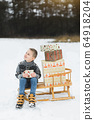 Cute little child, boy, sitting on a wooden sledge decorated with presents boxes, holding the box with small gift, outdoors in winter forest or park, snow wintertime 64918204