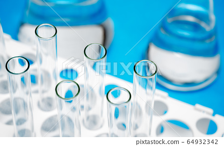 Close-up of the test tube on a blue background. 64932342