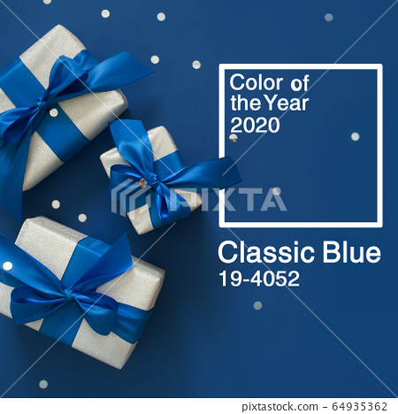 Festive Christmas decor on a blue classic background. Silver gift boxes, confetti, sparkles, ribbons, bows. Color of the year 2020. 64935362