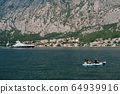 A married couple is kayaking, amicably rowing oars along Kotor Bay in Montenegro, against the background of the city of Dobrota, rocky mountains and a large expensive yacht. 64939916