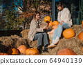 Girls have fun among pumpkins and haystacks on a city street 64940139