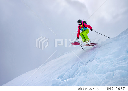 A girl in a green ski suit jumps from a snowy ledge against a cloudy sky in cloudy weather. Sun gleams through the clouds. The concept of winter sports and extreme 64943027